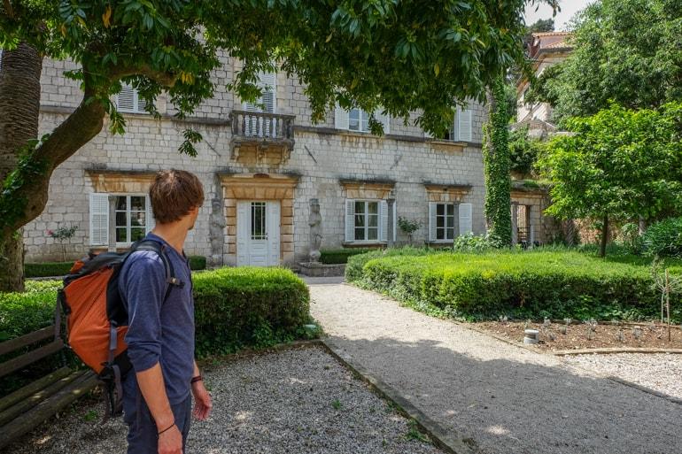 Mann mit Rucksack steht in Garten mit Haus im Hintergrund Dubrovnik Kroatien