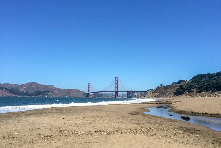 sandy beach with blue sky and bridge top 10 things to do in san francisco