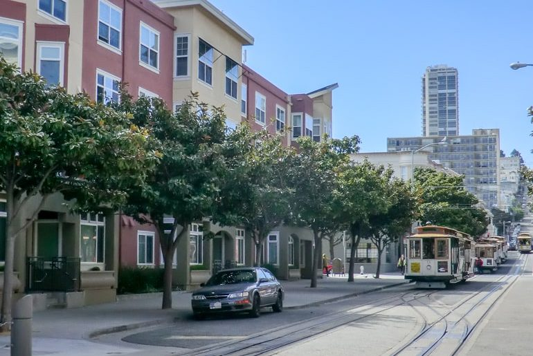 cable cars on street with green trees top 10 things to do in san francisco