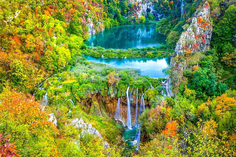 water fall with blue pool and autumn trees around plitvice lakes national park