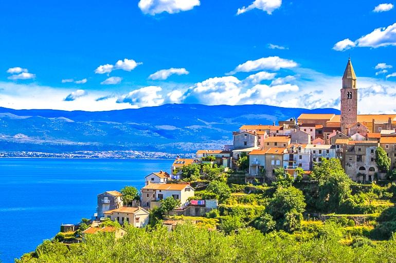 village with tower and orange roofs overlooking blue ocean and shoreline krk island croatia