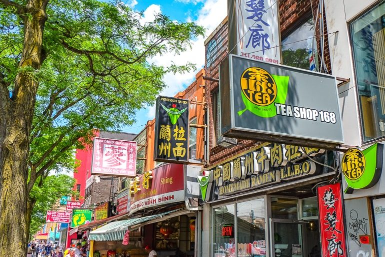 colourful signs with asian writing and green trees chinatown toronto tourist attractions