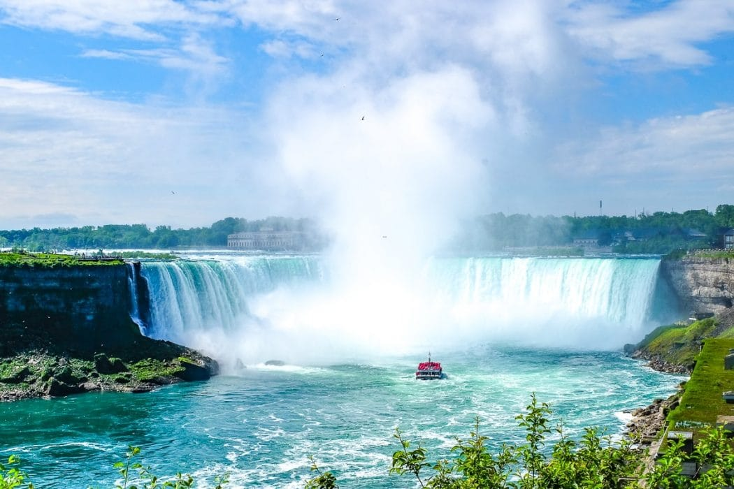 red boat approaching blue horseshoe waterfall niagara falls canada