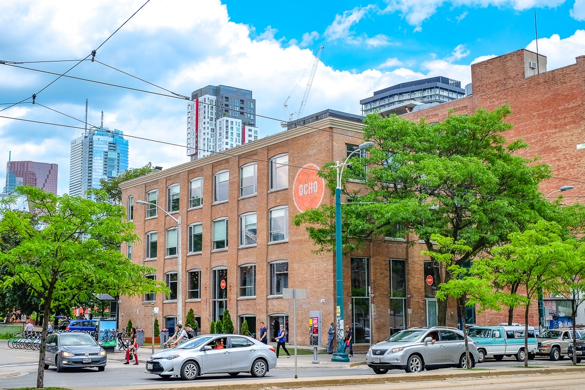 orange brick building with cars and trees in front where to stay in toronto