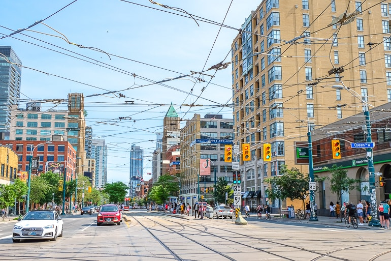 busy city intersection with cars and streetcar cables in toronto fashion district