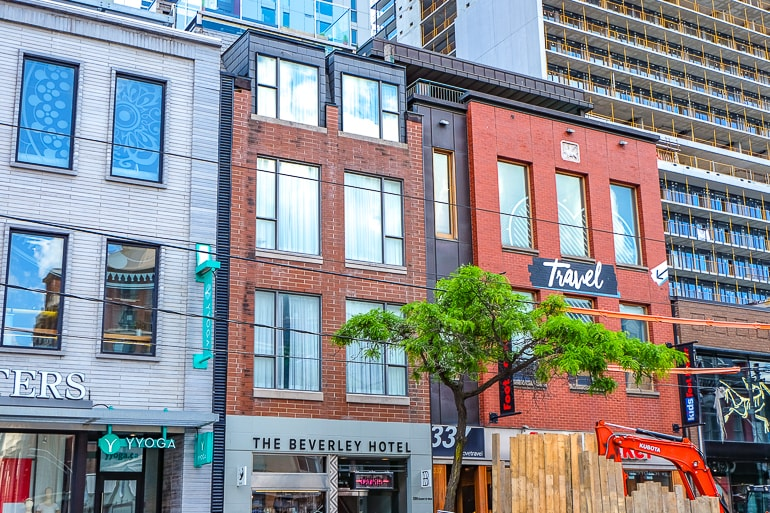 small hotel among brick buildings with shop fronts in toronto