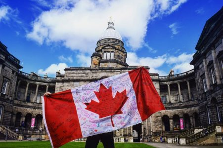 canada flag with old building and blue sky working holiday visa canada