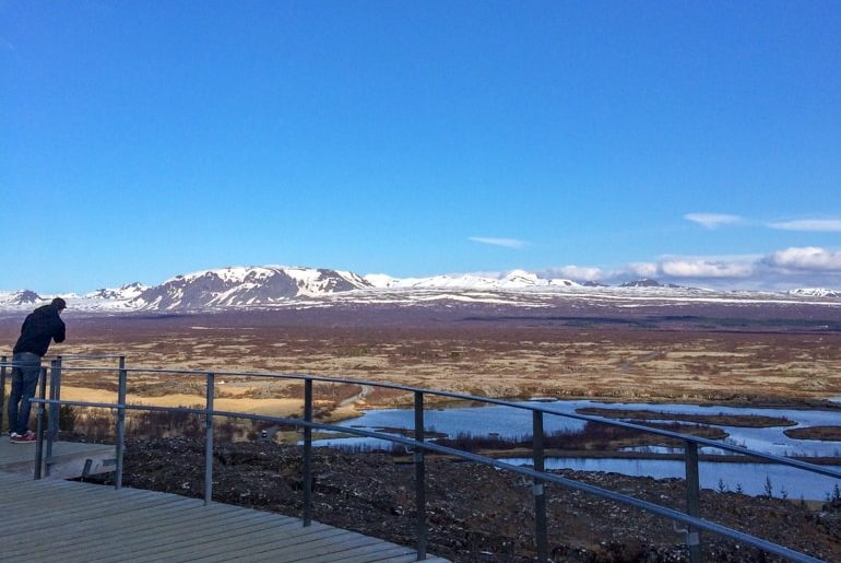 man standing on wood path overlooking iceland landscape golden circle tour