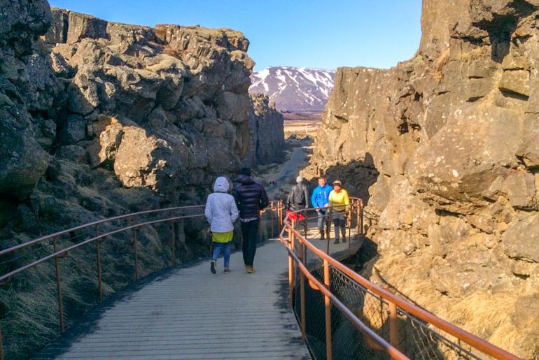people walking through rock cliffs on wooden path golden circle tour iceland