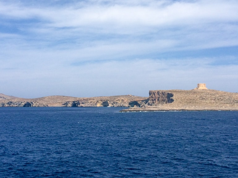 sandstone tower on island with blue ocean malta sightseeing