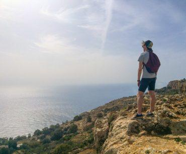 man standing on cliff edge with ocean below malta sightseeing