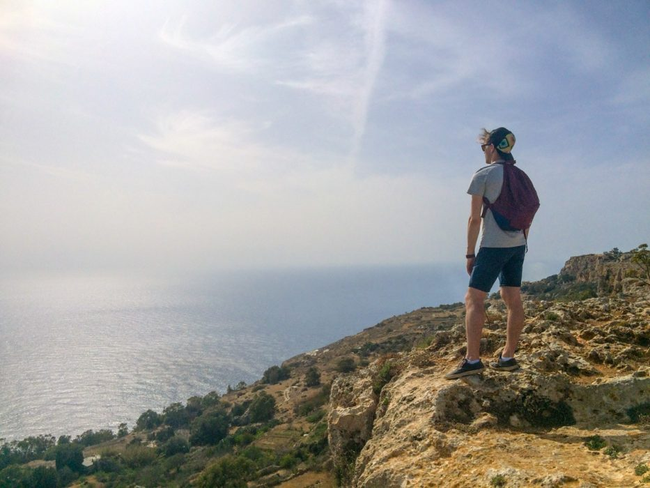 man standing on cliff edge with ocean below malta sightseeing