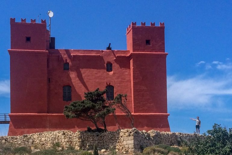 red castle tower with person beside malta sightseeing