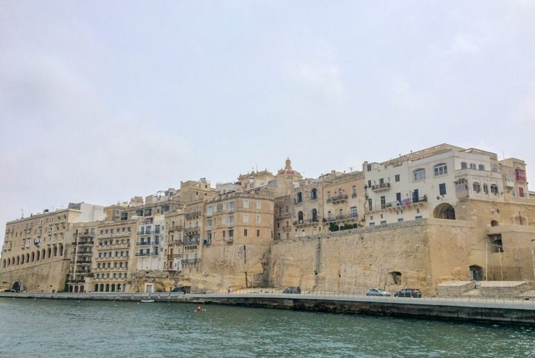 sandstone city with blue water below malta sightseeing