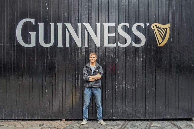 man in front of black guinness doors things to do in dublin