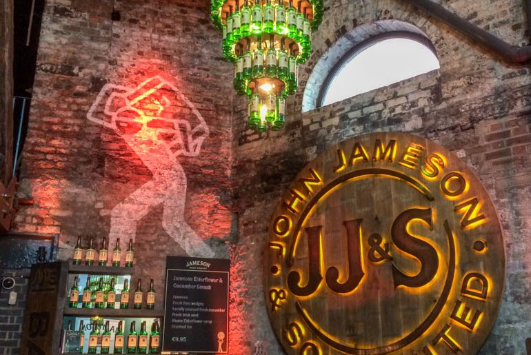 green glass bottles chandelier and sign things to do in dublin jameson