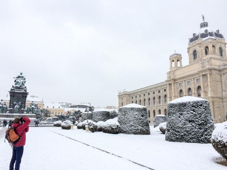 Mann in roter Jacke macht Foto von verschneitem Wien Österreich