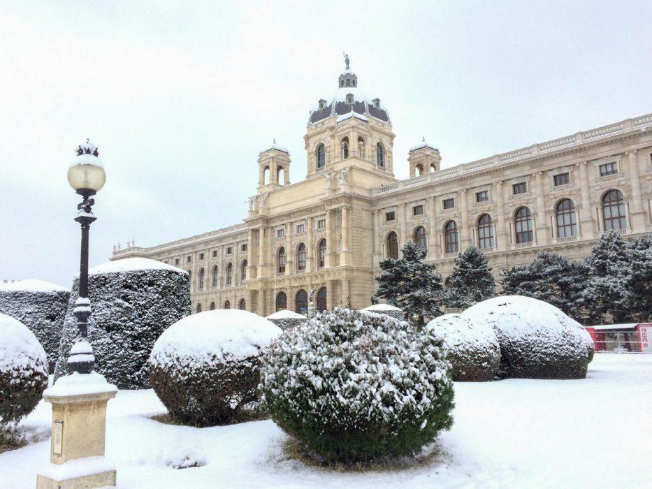 Altes Museumsgebäude mit schneebedeckten Büschen in Wien