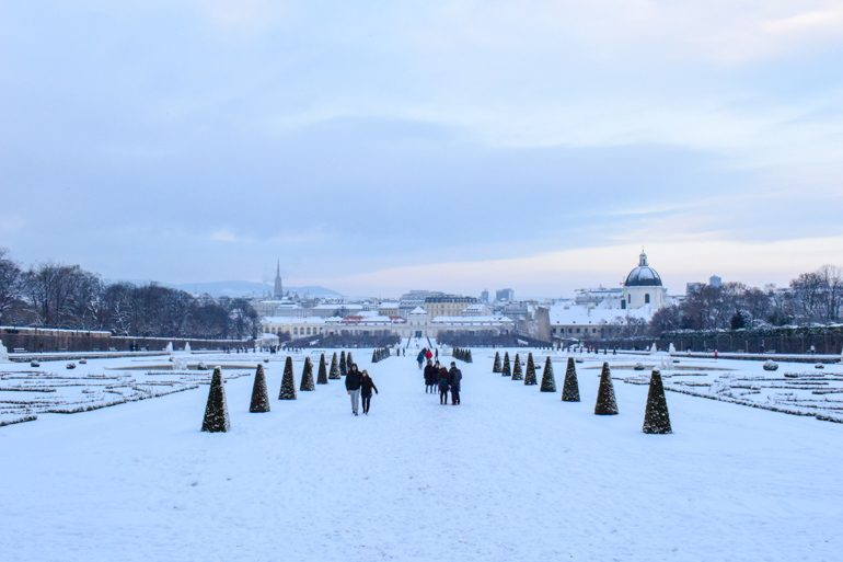 gardens with snowy ground and trees lining the path things to do in vienna