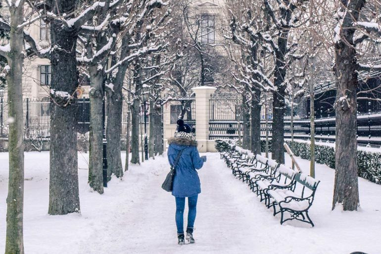 girl in blue parka wandering through snowy park things to do in vienna austria