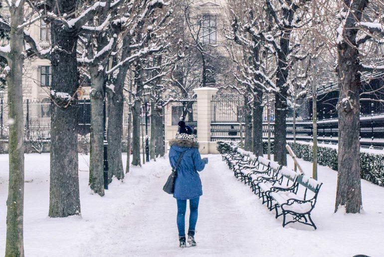 Frau in blauem Mantel läuft durch schneebedeckten Park Wien