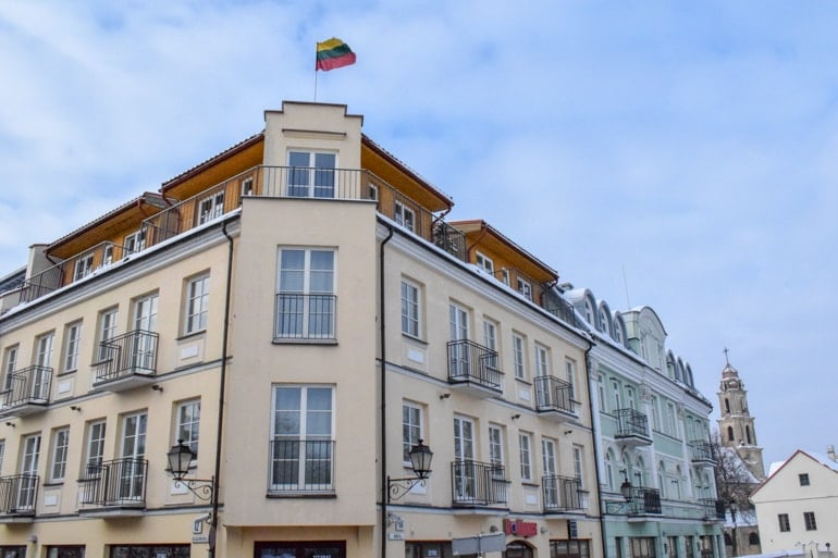 old colourful building with Lithuanian flag on top travelling the baltics
