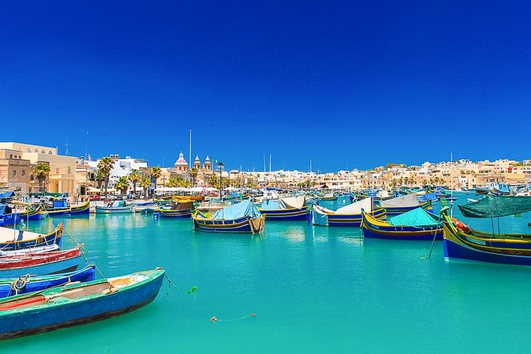 colourful boats in blue harbour with buildings behind marsaxlokk malta