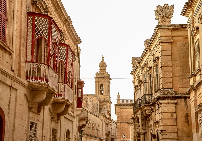stone alleyway with old tower and red windows mdina malta best place to stay