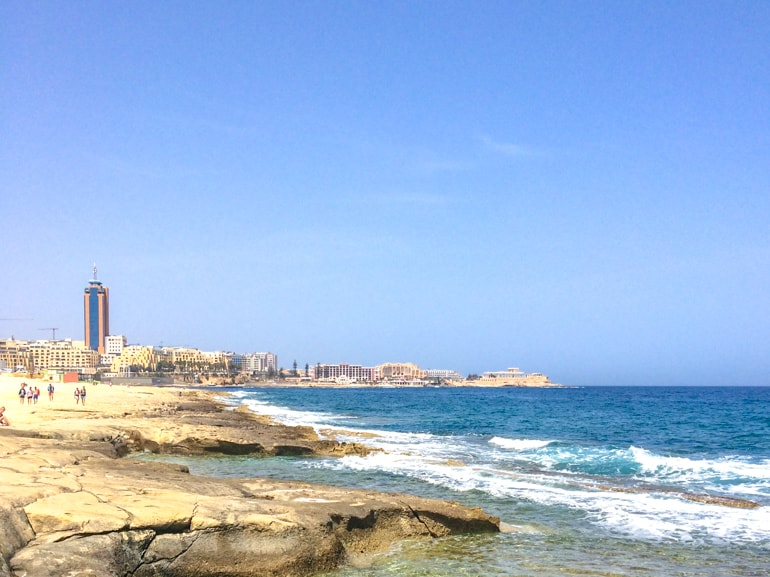 rocky shoreline with blue ocean and buildings in background best places to stay in malta st julians hotels