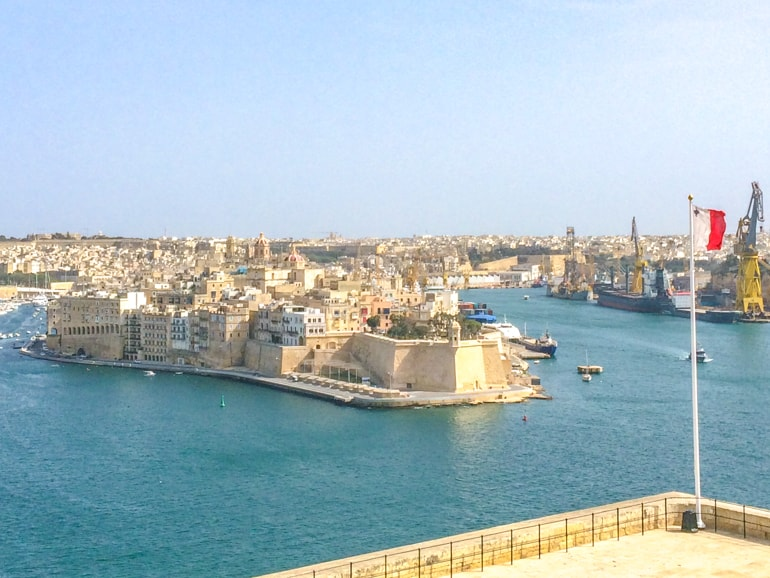 pier of old buildings in blue harbour with flag best places to stay in malta three cities
