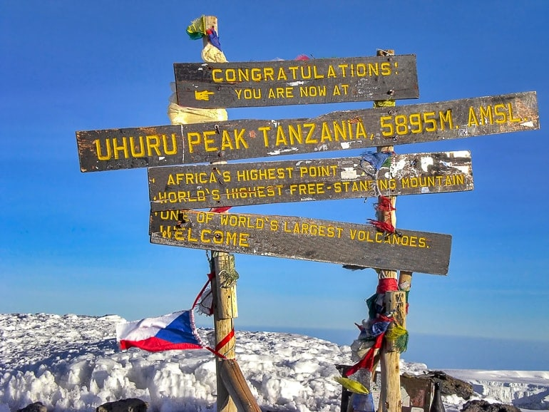 wooden signs and colourful flags on top of mountain experiences of a lifetime mount kilimanjaro