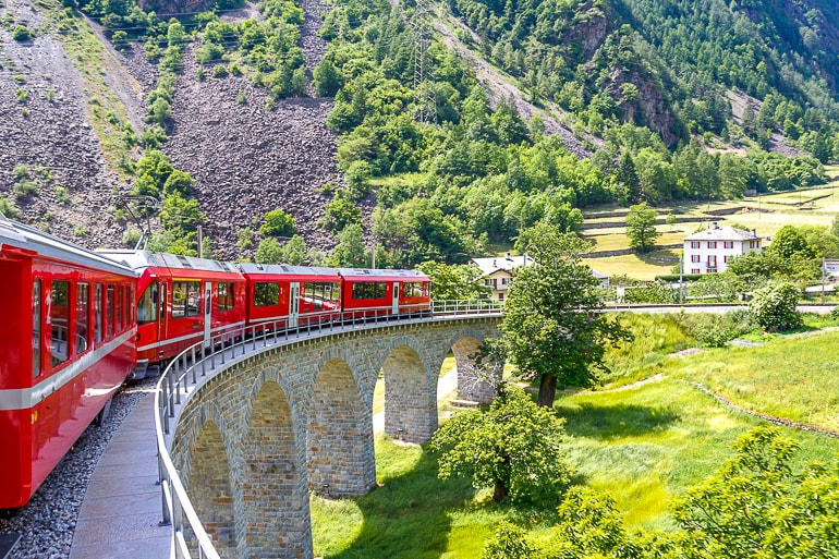 red train on curved bridge with green hills behind experiences of a lifetime switzerland