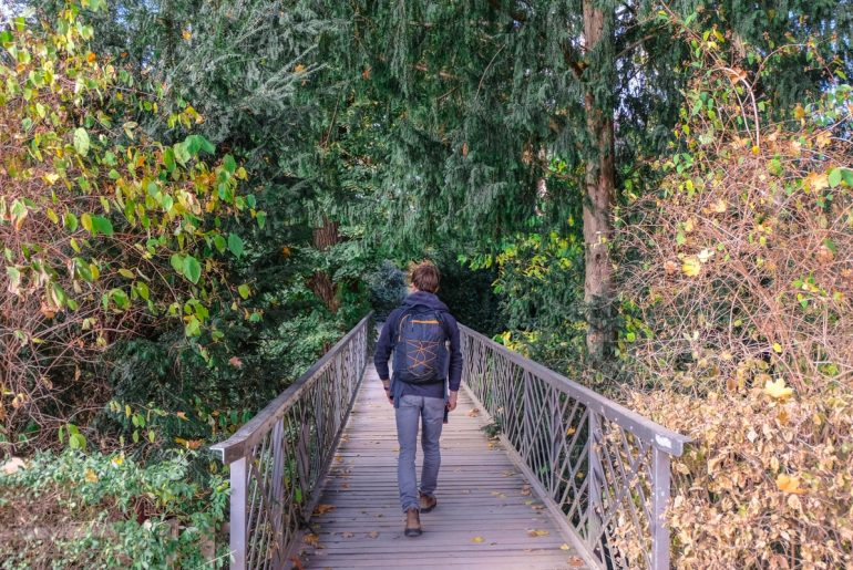 man with backpack walking along bridge in forest gifts for someone going travelling