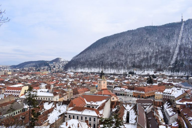 old town buildings with snow and mountain must see places in europe in winter brasov romania