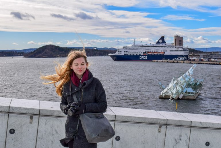 girl with windy blown hair and ship in harbour in background must see places in europe in winter oslo norway
