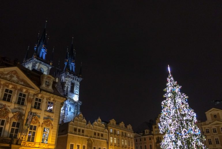 lit up christmas tree and church in night prague must see places in winter in europe