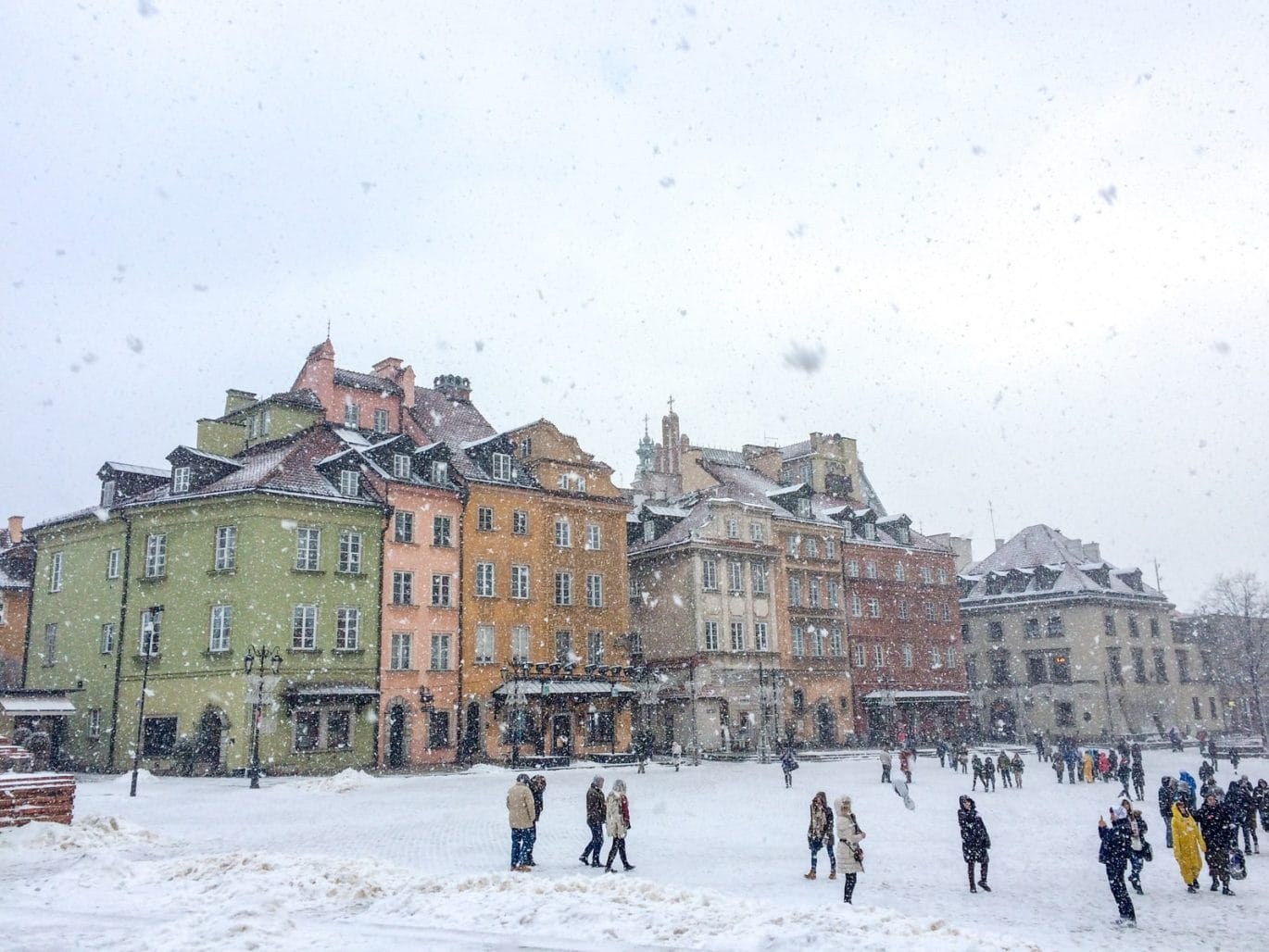 colourful buildings through snow flakes with people must see places in europe in winter warsaw