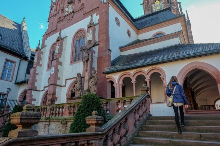 girl climbing stairs to decorated church exterior things to do in aschaffenburg Basilica of St. Peter and Alexander