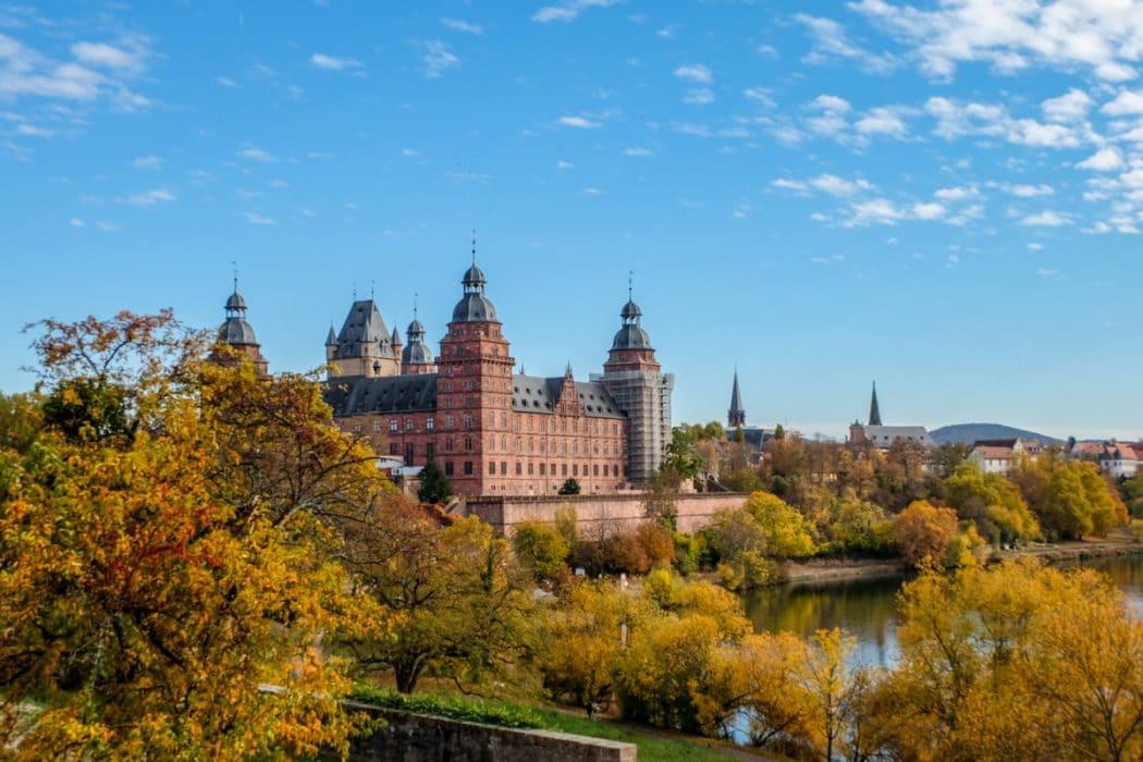 Rotes Schloss neben Bäumen in Herbstfarben und Fluss Aschaffenburg Bayern
