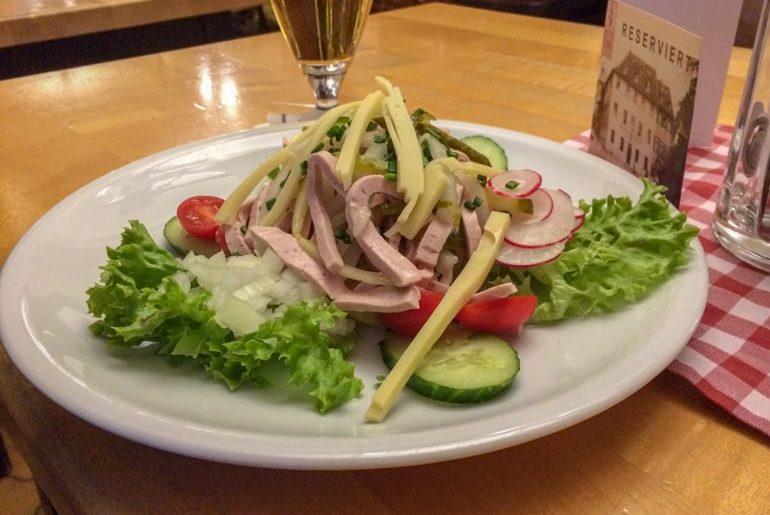 Wurstsalat aus weißem Teller mit Käse fränkische Hausmannskost