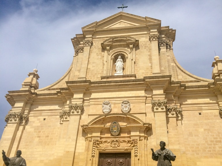 stone church front with statues and blue sky things to do in gozo