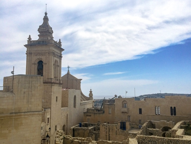 stone tower and old citadel walls with blue sky things to do in gozo citadella