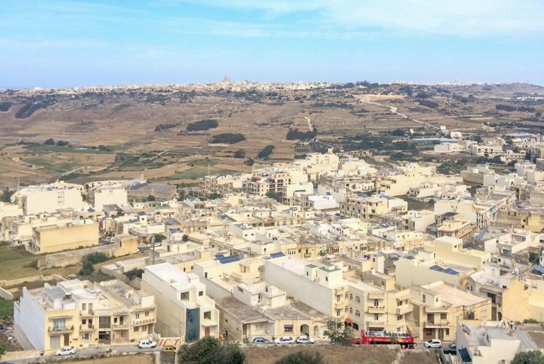stone buildings from up top on high city walls with cars on road things to do in gozo bus tour