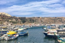 boats in harbour with blue water things to do in gozo