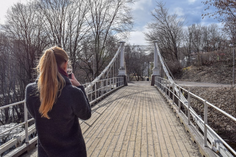 girl taking photo of wood suspension bridge things to do in oslo norway