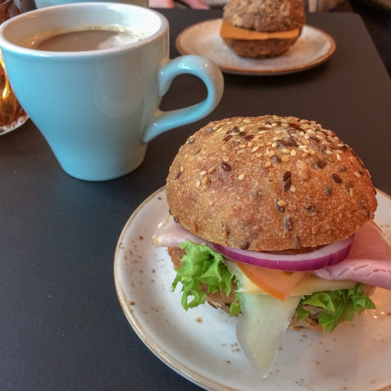 small sandwich on bun with coffee mug things to do in oslo norway