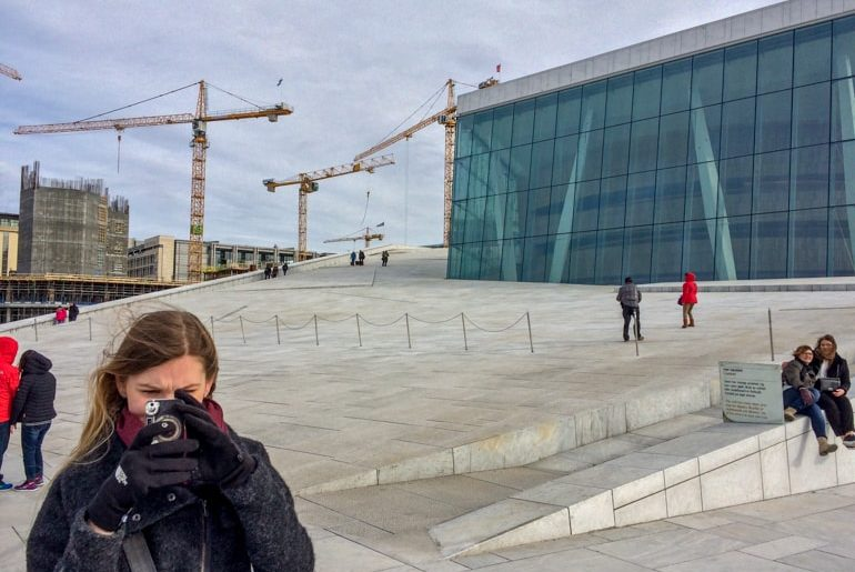 girl taking photo with phone on roof with cranes behind things to do in oslo norway