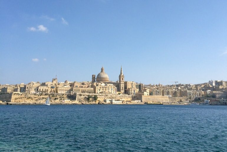 large domed church among smaller buildings and blue water things to do in valletta