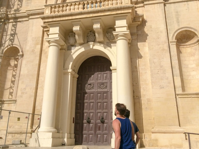 brown door and stone pillars with men gazing things to do in valletta