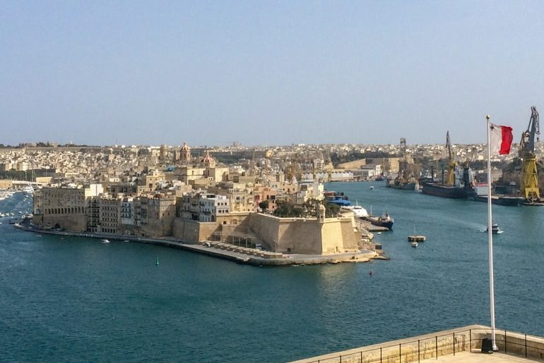 blue water harbour with city peninsula and flag flying in front things to do in valletta